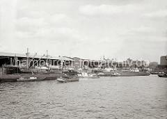 Blick zum Dalmannkai des Grasbrookhafens, der 1881 parallel zum Sandtorhafen verlaufend fertig gestellt wurde. Die Ladung der Frachtschiffe wird über die Hafenkrane gelöscht oder die Frachter werden neu beladen.