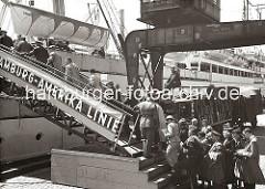Schiffs-Passagiere gehen über die Gangway an Bord eines Passagierschiffs der Hamburg-Amerika-Linie HAPAG, das im Hamburger Baakenhafen fest gemacht hat. Von der Reling beobachten Schiffsoffiziere und andere Fahrgäste das Geschehen auf dem Versma