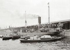 Der Frachter GANNET mit Heimathafen London liegt im Grasbrookhafen am Dalmannkai und wird be- und entladen. Mehrere beladene Schuten haben am Schiff fest gemacht. Am Bordkran des Frachters hängt eine Ladung Kisten.