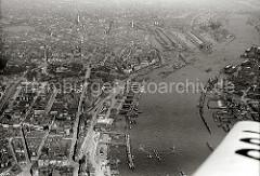 Historische Luftaufnahme von Hamburg und den St. Pauli Landungsbrücken. In der linken Bildhälfte dei St. Michaeliskirche, rechts der Zollkanal an der Speicherstadt und der Sandtorhafen / Grasbrookhafen. Dahinter das Gasometer der Gaswerke.
