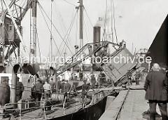 Ein Rollkran hat beim Löschen eines Frachtschiffs Übergewicht bekommen und ist auf das Deck des Frachters gekippt. Feuerwehrleute und Kaiarbeiter legen eine Stahl-Trosse um den Kran, damit der auf der Wasserseite des Schiffs liegende Schwimmkran