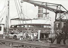 Das Automobil mit dem Kran am Hübenerkai des Hamburger Grasbrookhafens an Bord eines Norwegischen Schiffs verladen. Das Logo der Reederei Bergenske Dampskibsselskap (BDS) ist unter dem Fenster der Brücke des Schiffs angebracht.