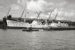 Ein Schlepper schleppt ein Binnenschiff der tschechoslowakischen Schifffahrtsgesellschaft C.P.S.L. durch den Baakenhafen Richtung Elbe. Am Versmannkai liegt der schwedische Fruchtfrachter EGYTIAN REEFER - seine Ladung wird in den Fruchtschuppe