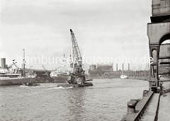 Der Schwimmkran hat den verunglückten Rollkran an Deck gehievt und fährt mit eigenem Antrieb durch den Baakenhafen Richtung Elbe. Im Hintergrund das Gasometer und die Schornsteine der Hamburger Gasanstalt auf dem Großen Grasbrook.