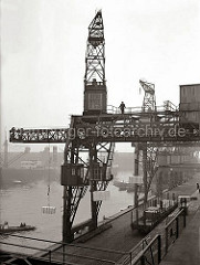 Ein Dreifachkran transportiert vor dem Hafenschuppen 83 im Hamburger Oderhafen drei Kisten an Land. Vor der Laderampe steht ein offener Güterwaggon beladen mit Kisten - auf der Rampe stehen ein Elektrohubwagen und Sackkarren.