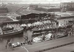Luftfoto vom Rosshafen im Hamburger Hafen; Frachtschiffe liegen an den Dalben. Die Ladung eines der Frachter wird über Binnenschiffe und Kähne, die längseits fest gemacht haben gelöscht. Links im Hintergrund Helgen der Howaldtswerft und im Hi