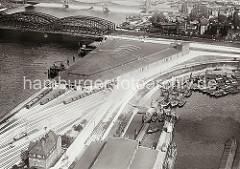 Luftbild Verteilungszentrum am Holthusenkai / Norderelbe - Güterzüge stehen vor den Einfahrten in das dreieckige Hafengebäude. Lks. im Hintergrund die Norderelbbrücken und Wohnbebauung auf der Veddel. Im Vordergrund Binnenschiffe und Schuten