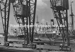 die Kräne im Hamburger Hafen laufen auf Schienen - im Vordergrund der Kai Breslauer Ufer im Oderhafen. Schiffe liegen auf Reede im Hafen; Schuten und Binnenschiffe haben an der Bordwand fest gemacht.