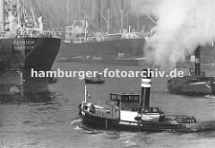 Frachtschiffe liegen im Kaiser-Wilhelm-Hafen - im Vordergrund dampft ein Hafenschlepper durch das Hafenbecken; lks. wird ein Binnenschiff von einem Schlepper geschleppt, dicker Qualm steigt aus dem Schornstein des Arbeitsschiffes. In der Bildmitte