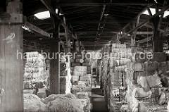 Im Lagerhaus C des Melniker Ufers im Hamburger Moldauhafen sind mit Bandeisen verschnürte Wollballen bis unter die Decke des Speichers gelagert. Licht fällt über die Oberlichter auf die Güter - für den Nachtbetrieb hängen Lampen an der Decke über