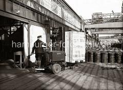 Ein Lagerarbeiter hat eine große Holzkiste auf die Gabel des Elektrohubwagen geladen und fährt sein Transportgut auf die Lagerrampe des Schuppens 83 am Chilekai des Oderhafens. Auf der Rampe stehen Metallfässer, im Hintergrund ein Arbeiter mit ein