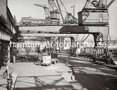 Ein Elektrokarren steht auf der Laderampe des Chilekais im Hamburger Oderhafen. Zwei Holzkisten sind auf dem Anhänger des Transportfahrzeugs von den Kaiarbeitern gestapelt worden. An der Laderampe steht ein mit Paketen voll beladener Güterzug.