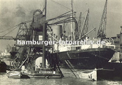 Ein schwimmender Getreideheber arbeitet längsseits eines Frachtschiffs im Kaiser-Wilhelm-Hafen - über lange Saugvorrichtungen werden Massengüter wie z. B. Getreide aus dem Laderaum des Frachtschiffe pneumatisch gelöscht. Über eine Schüttvorrichtun