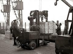 Eine große Holzkiste ist mit einem Elektrohubwagen der AEG von seinem Fahrer auf die Rampe des Schuppen 83 am Chilekai des Hamburger Oderhafens transportiert worden. Hafenarbeiter legen Tauwerk um die Kiste, an dem der fahrbare Kran sie auf den be