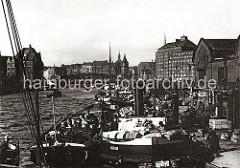Breite Frachtkähne liege nebeneinander am Ponton des Hamburger Gemüsemarkts am Deichtor; die Ladung der Schiffe besteht aus Kisten, Körben und Holztonnen, in denen die Ware für den Markt angeliefert wird.
