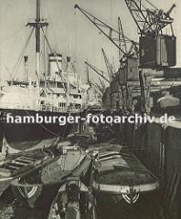 Frachter am Auguste Victoria Kai im Kaiser Wilhelm Hafen im Hamburger Hafen. Schuten liegen an der Kaimauer und können so mit der Fracht beladen werden. Im Vordergrund bewegt eine Barkasse einen leeren Frachtkahn. Auf dem Kai stehen Kräne.