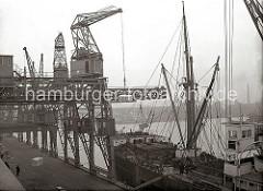 Ein Frachter liegt am Schuppen 82 des Chilekais im Oderhafen, eines der vielen Hafenbecken im Hamburger Hafen. Über einen Dreifachkran werden grosse Frachtkisten an Bord des Schiffes gebracht. Im Hintergrund die Kaischuppen am Mönckebergkai des El