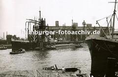 Ein Getreidefrachter liegt an der Pier im Kuhwerder Hafen; die langen Saugrüssel des Getreidehebers sind in den Laderaum des Frachters gesteckt und befördern die Ladung an Land. Auf der anderen Seite des Stegs liegen Binnenschiffe, die über eine S