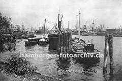Blick vom Lübecker Ufer in den Hansahafen - im Hintergrund die Schornsteine der Frachtschiffe, die am Oswaldkai liegen und deren Ladung gelöscht wird. Im Vordergrund hölzerne Duckdalben, die aus langen Baumstämmen gefertigt werden und tief in den