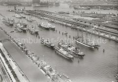 Frachterschiffe und zwei Frachtsegler liegen an den Dalben in der Mitte des Hafenbeckens vom Segelschiffhafen, bei einigen Schiffen wird die Ladung über Schuten gelöscht. In der rechten oberen Bildhälfte der Moldau Hafen mit dem Veddel Höft.