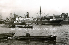 Schlepper ziehen jeweils zwei Schuten durch den Ellerholzhafen - ein Frachter liegt am Mönckebergkai und löscht seine Ladung auf längsseits liegende Boote. Rechts im Hintergrund die im Hamburger Hafen typische Industriearchitektur mit Turm - das G