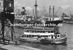 Ein Schiff der Hamburger Hafenrundfahrt fährt die Hamburg Touristen durch den Oderhafen - auf dem oberen Deck der GODEFFROY stehen die Hamburg-Besucher und beobachten das Geschehen in Hamburgs Hafen. Im Vordergrund ein fahrbarer Hafenkran am Bresl