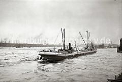 Ein Motorschiff fährt in den Moldauhafen ein - hinter dem Bug ist das Veddelhöft zu erkennen. Im Hintergrund überspannt die eiserne Bogenkonstruktion der Freihafen-Elbbrücke den Hamburger Fluss; am gegenüber- liegenden Ufer der Kirchenpauerkai