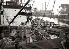 Ein Frachtschiffs nimmt im Oderhafen Ladung auf - über bordeigene Ladebäume werden Säcke von den längsseits liegenden Schuten und Lastkähne gehievt. Im Vordergrund nehmen zwei Schauerleute die Hieve Säcke, die an einem Kranhaken hängt entgegen. Im