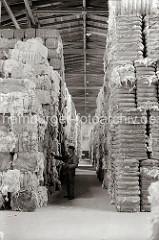 Im Lagerhaus C des Melniker Ufers im Hamburger Moldauhafen werden mit Bandeisen verschnürte Wollballen gelagert; ein Lagerarbeiter prüft die Lagerware.