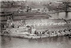 Luftfoto von Lagerschuppen im Hamburger Hafen - im Vordergrund der Kaischuppen 21 am Auguste Victoria Kai des Kaiser Wilhelm Hafens; dahinter der Schuppen 70 am Grevenhof Ufer des Kuhwärder Hafens.