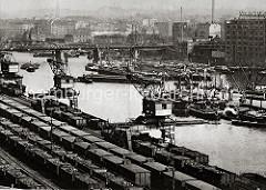 Dampffrachter und Binnenschiffe liegen im Billehafen; einige von den grossen Lastkähnen liegen in der Mitte des Hafenbeckens. Ein Hafenschlepper zieht vier mit Kohle hoch beladene Schute bei der Eisenbahnbrücke über das Wasser des Billehafens