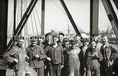 """Die Schauerleute im Rosshafen machen eine Pause, einige haben eine Pfeife in der Hand, die meisten tragen einen """"Elbsegler"""", die typische Hamburger Schirmmütze. Die Aufgabe der Schauerleute besteht im Stauen bzw. dem Be- und Entladen der Frachtschif"""