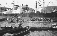 Das Frachtschiff DORA OLDENDORFF liegt in der Mitte des Roßhafens an den Dalben. Schuten mit Kisten an Bord haben längsseits fest gemacht. Im Vordergrund warten Ewerführer mit ihren Kähnen mit Hilfe des Schleppers auf ihren Arbeitseinsatz.