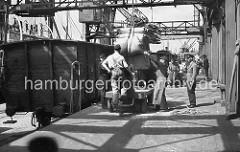 Arbeit im Hamburger Hafen ca. 1948; ein Frachter wird im Roßhafen gelöscht. Der Kran bringt die Säcke aus dem Laderaum des Schiffs an Land - Kaiarbeiter nehmen die Ladung in Empfang. Auf einem Elektrokarren werden die Säcke in den Lagerschuppen geb