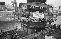 Verladung von einer fabrikneuen Dampflokomotive im Hamburger Hafen; die in den Henschel-Werken gebaute Lok wird im Ellerholzhafen am Mönckebergkai mit einem Schwimmkran von den Gleisen gehoben.