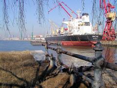 Altes Geländer an der ehem. Durchfahrt vom Kaiser-Wilhelm-Hafen zum Ellerholzhafen - im Hintergrund ein Frachtschiff unter Hafenkränen (2002).