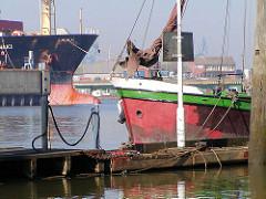 Schiffsbug eines Segelschiffs im Travehafen / Roeloffs Ufer; im Hintergrund ein Frachschiff am Sthamerkai vom Oderhafen / Oderhöft.