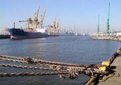 Blick über den Kaiser-Wilhelm-Hafen vom Auguste-Victoria-Kai zum Kronprinzenkai (2002). Taue eines Frachtschiffs an einem Poller - Frachter unter Hafenkränen.