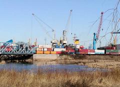 Der Ellerholzkanal, die Verbindung zwischen dem Rosshafen und dem Rodewischhafen / Travehafen wird ab 2000 zugeschüttet, die Brücken sind geblieben, dahinter das Buss Hansa Terminal, Containerlager und Kräne. (2002)