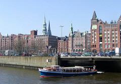 Eine Barkasse kommt vom Brooksfleet und fährt in den Brooktorhafen ein - am Ufer der Zollzaun des Hamburger Freihafens.