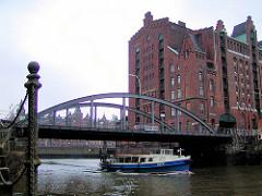 Magdeburger Brücke über den Magdeburger Hafen in der Hamburger Hafencity  - ein Fahrgastschiff / Barkasse fährt unter der Brücke Richtung Elbe; im Vordergrund Eisenpfeiler und Eisenkette einer Wassertreppe - re. der Kaispeicher B.