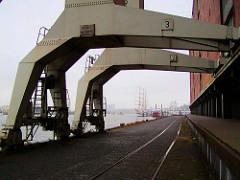 Alte Ansicht von den Portalkränen beim Kaispeicher A an der Elbe in der Hamburger Hafencity. Im Hintergrund Segelschiffe bei den Landungsbrücken.