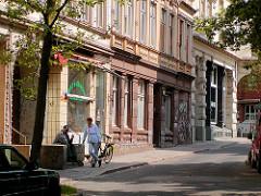 Historische Gebäude in der Trommelstrasse auf Hamburg St. Pauli - Idylle in einer Seitenstrasse, leerstehende Geschäfte - Menschen auf der Treppe in der Sonne. Die Gebäude wurden 2004 abgerissen.