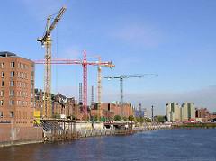 Beginn der Bauarbeiten an der Hamburger Hafencity am Sandtorkai - Baukräne, dahinter die Speicherstadt und das Kesselhaus. (2003)