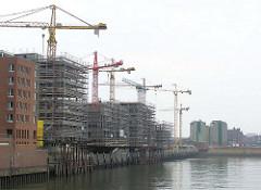 Rohbauten und Baukräne am Sandtorkai in der Hamburger Speicherstadt / Hafencity, Blick über das Hafenbecken vom Sandtorhafen zum Lagergebäude der Kaffeelagerei, dahinter der Kaispeicher B. (2004)