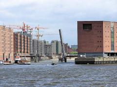 Einfahrt in den Sandtorhafen in der Hamburger Hafencity - Baustellen / Baukräne am Sandtorkai; im Hintergrund das Kaffeesilo am Brooktorkai. Die Klappbrücke ist hochgefahren, re. der Kaispeicher A.