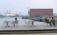 Terrasse mit Stühlen am Grasbrookhafen - im Hintergrund der Kaispeicher A und die Norderelbe. ( 2004 )