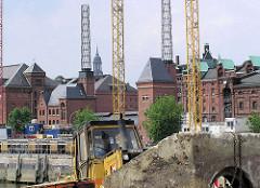 Sandarbeiten, Bagger an der Baustelle der Magellan-Terrassen im Hamburger Sandtorhafen - Baukräne am Sandtorkai; Speichergebäude und Kesselhaus. (2004)