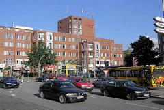 Straßenverkehr auf dem Winterhuder Marktplatz im Hamburger Stadtteil  Winterhude - Gebäude Forum Winterhude; Einkaufszentrum und Bürogebäude / Wohnungen.