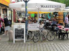 Restaurant mit Tischen auf dem Winterhuder Marktplatz im Hamburger Stadtteil  Winterhude